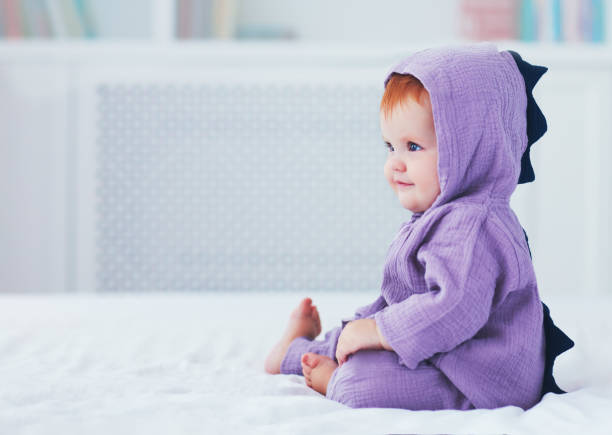 beautiful smiling, nine month old, infant baby girl in dinosaur costume, is sitting on the bed stock photo