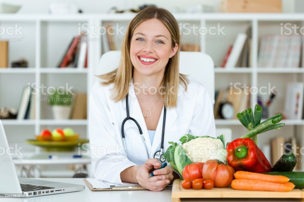 Beautiful smiling nutritionist looking at camera and showing healthy vegetables in the consultation. stock photo