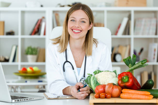 beautiful smiling nutritionist looking at camera and showing healthy vegetables in the consultation. - mangiare sano foto e immagini stock