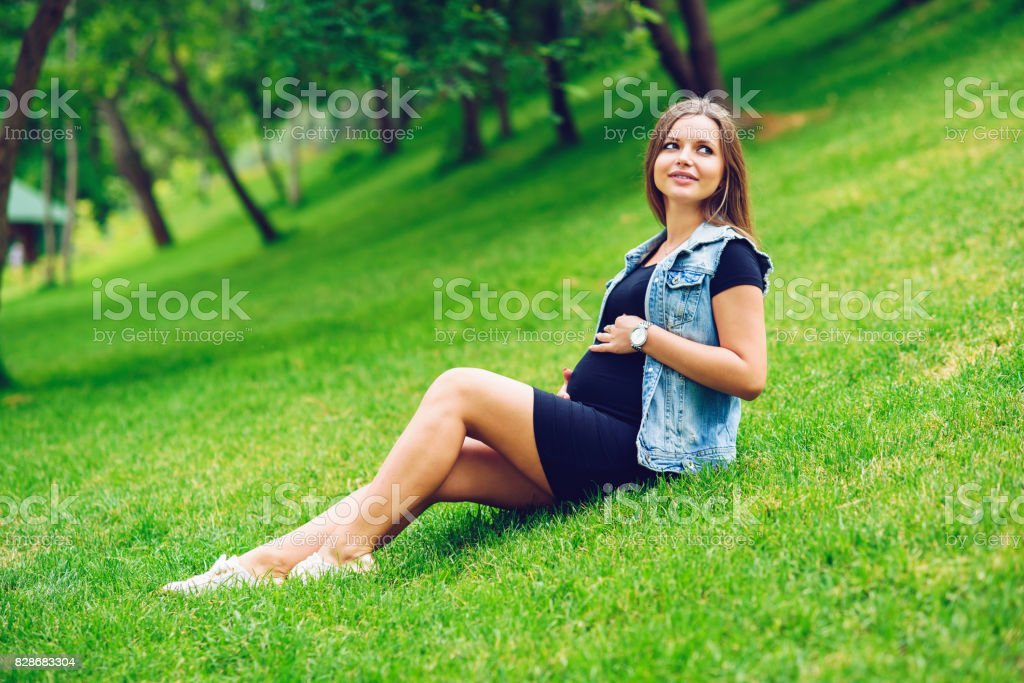efd927c510a52 A beautiful smiling pregnant woman in a black tight dress and blue jeans  jacket sitting on green grass in park and touching her belly with love and  care.