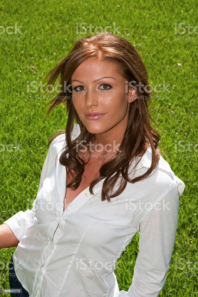 Beautiful smiling redhead woman with white blouse against green grass royalty-free stock photo