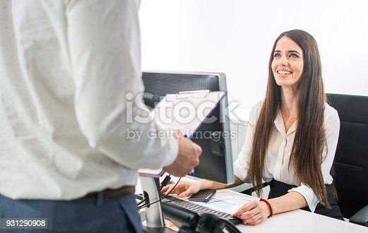 istock Beautiful smiling secretary welcoming client at office reception desk. 931290908
