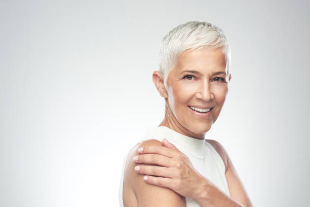 Beautiful smiling senior woman with short gray hair posing in front of gray background. Beauty photography. stock photo