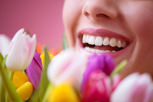 Beautiful Smiling Woman Behind Tulips stock photo