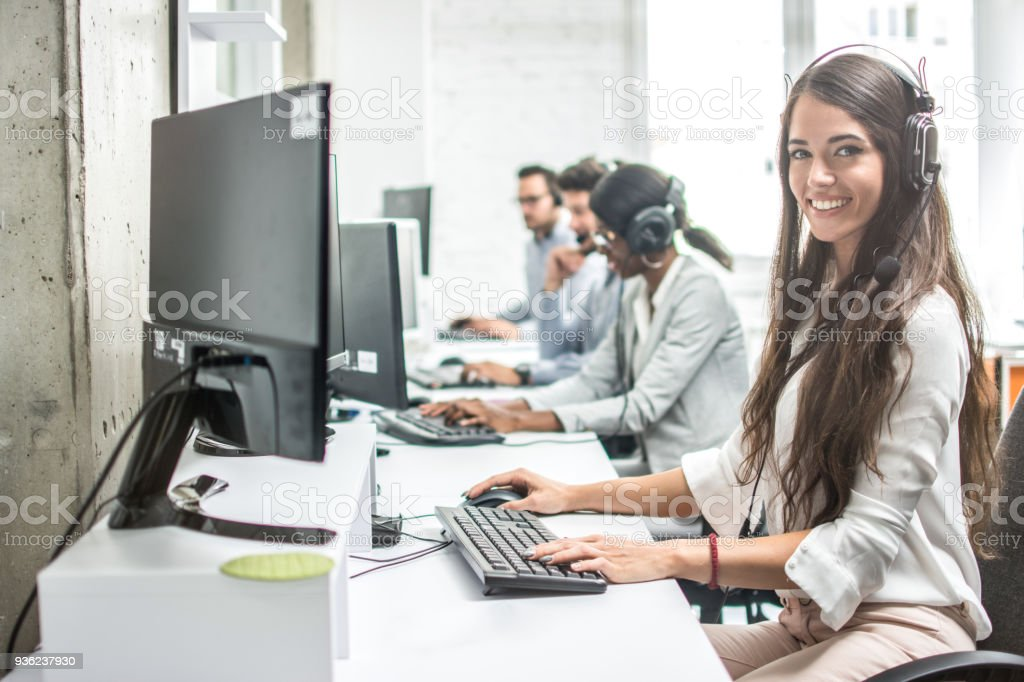 Beautiful smiling woman costumer support worker with headset using computer in call center. stock photo