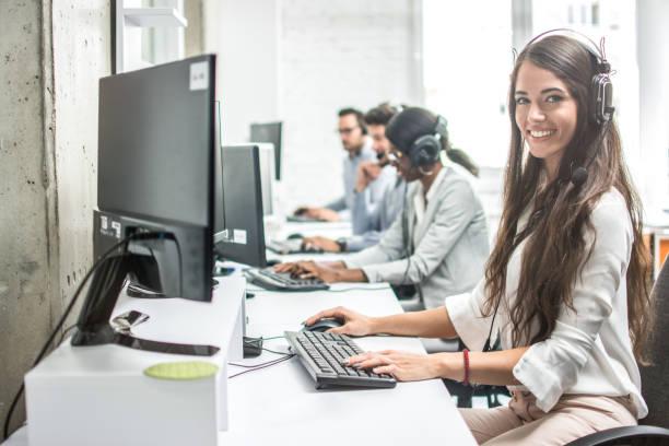 linda sorridente mulher cliente apoio trabalhador com fone de ouvido usando o computador em call center. - costumer - fotografias e filmes do acervo