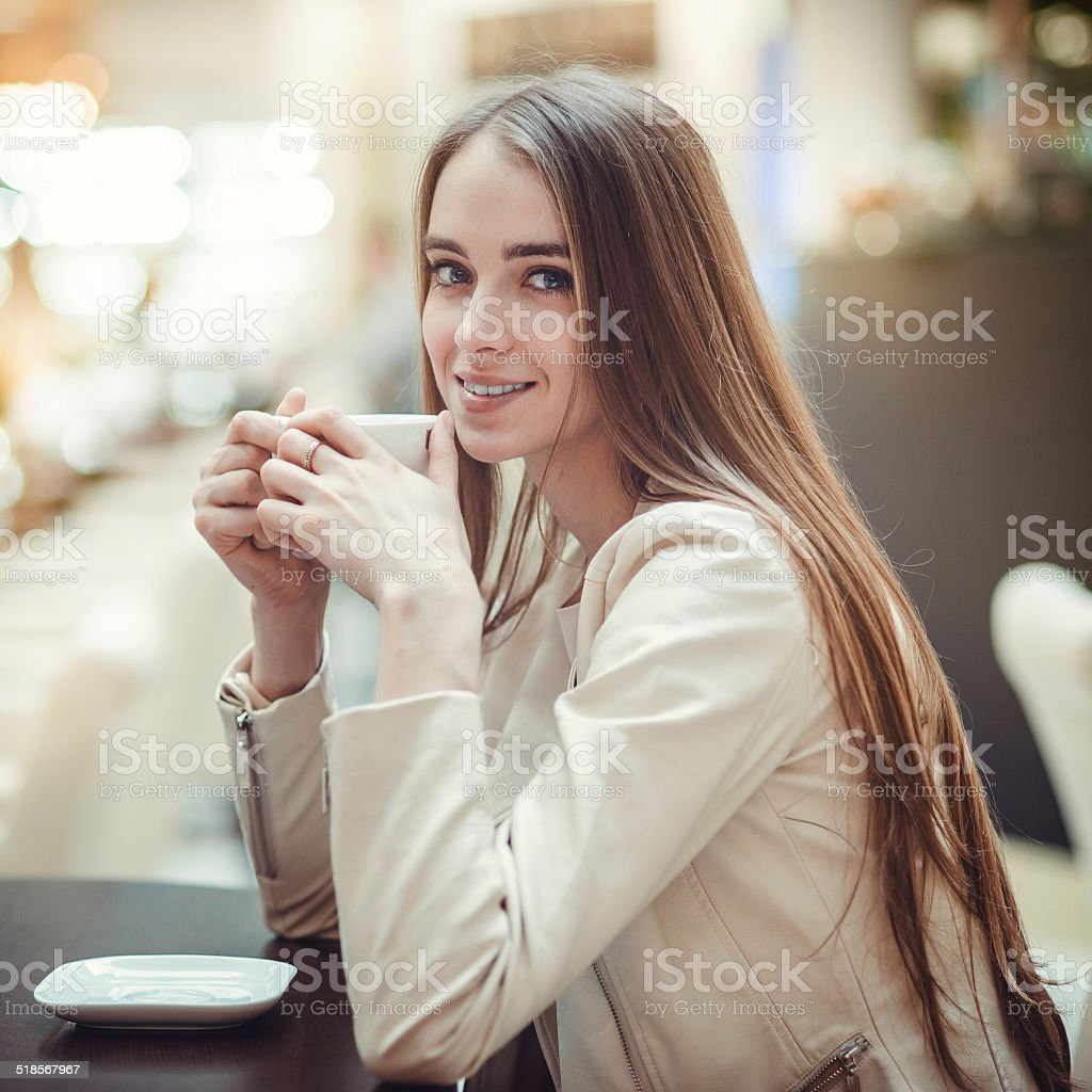 Beautiful smiling woman drinking coffee in cafe stock photo