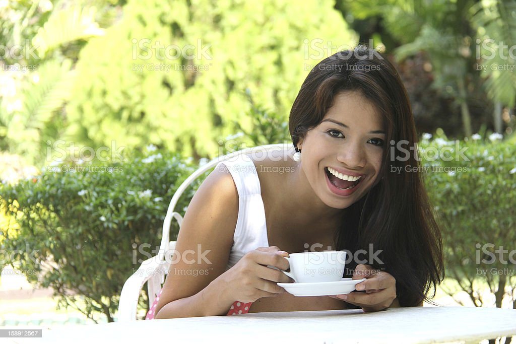 beautiful smiling woman drinking coffee or tea in the garden stock photo