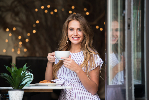 Beautiful smiling woman drinking coffee with croissant at the cafe