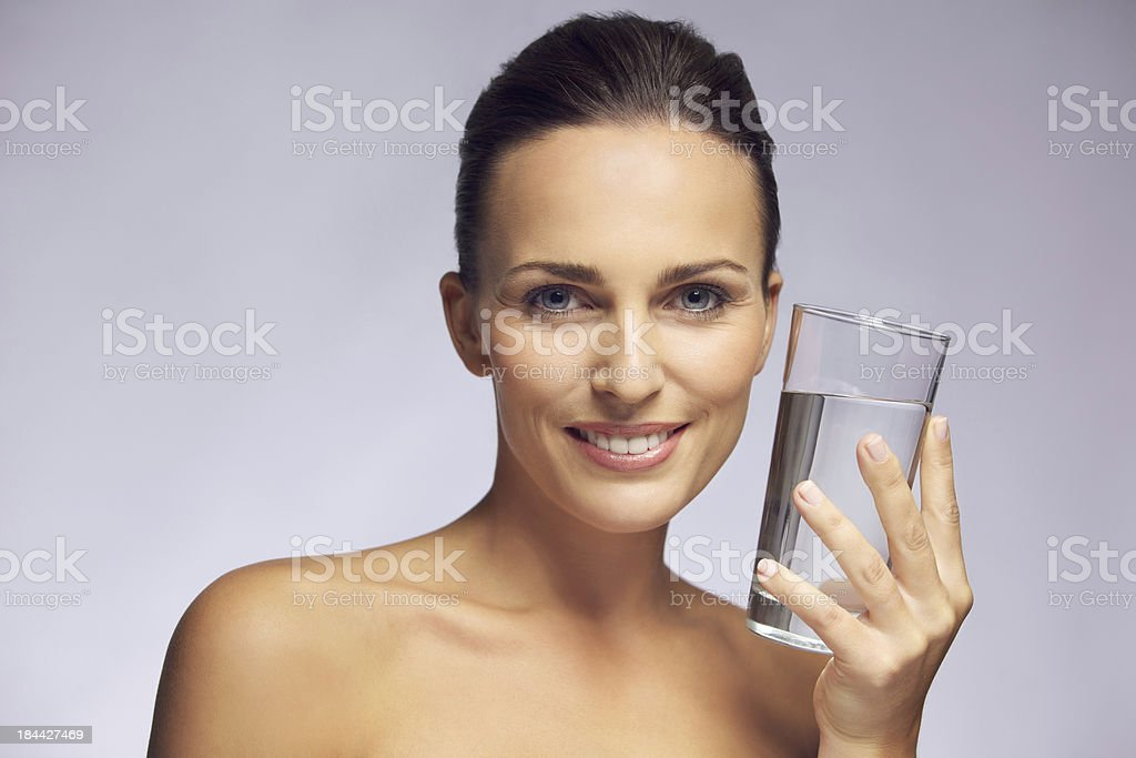 Beautiful smiling woman holding a glass of pure water royalty-free stock photo