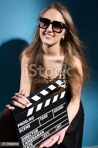 istock Beautiful smiling woman holding a movie clapper 512593616