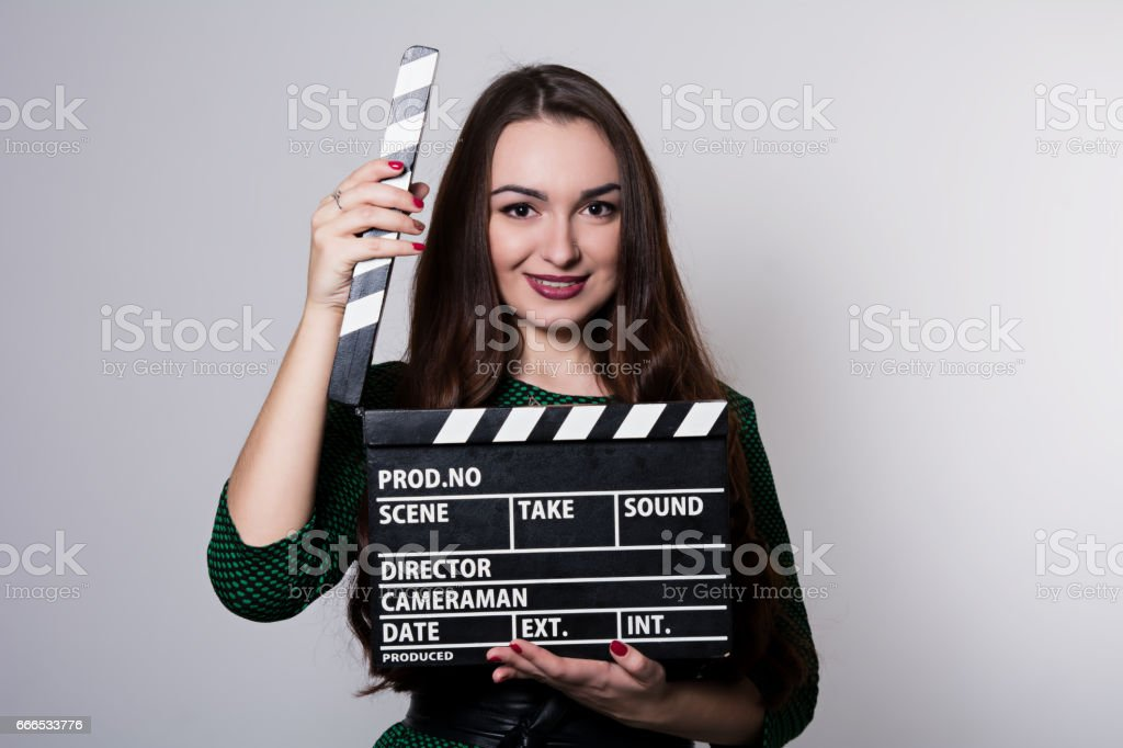 Beautiful smiling woman holding a movie clapper. stock photo