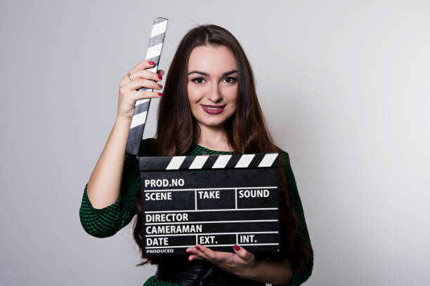 beautiful smiling woman holding a movie clapper. - audition stock photos and pictures