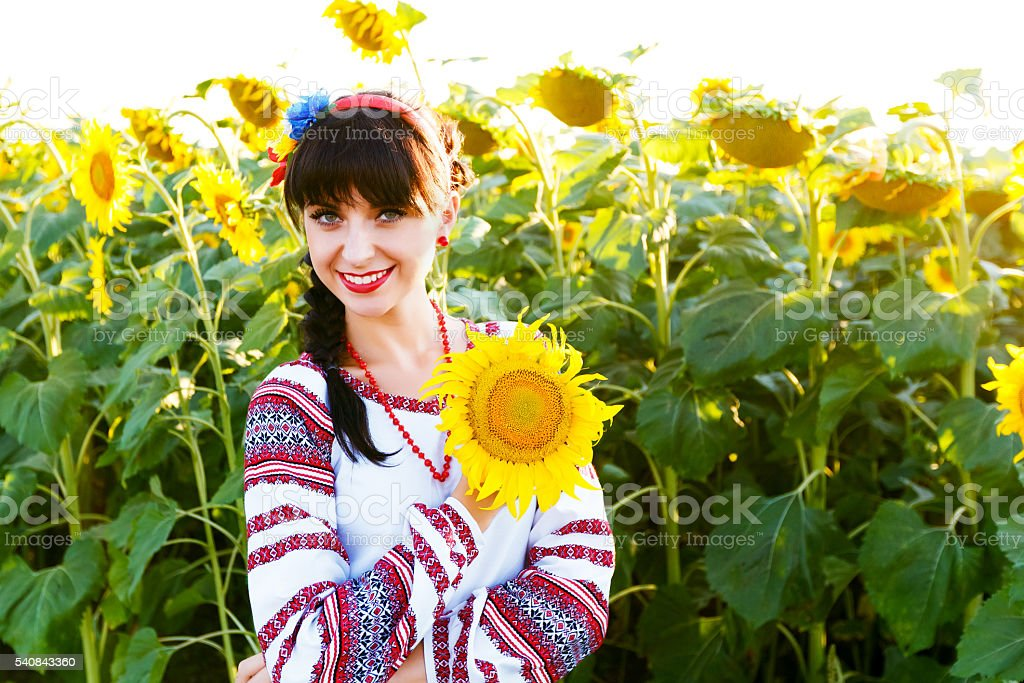 Beautiful smiling woman in  embrodery holding a sunflower stock photo