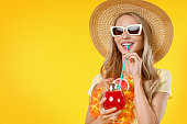 istock Beautiful smiling woman in summer dress with cocktail isolated on yellow background 1202302053