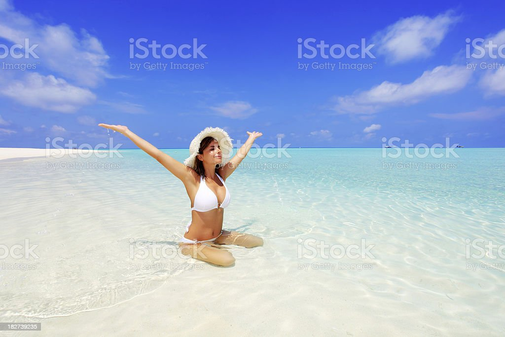 Beautiful smiling woman in the sea with raised hands. royalty-free stock photo