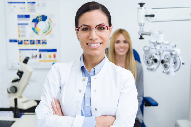 Beautiful smiling woman looking at camera in ophthalmology clinic with woman patient sitting for eye test in background. Portrait of beautiful smiling woman looking at camera in ophthalmology clinic with woman patient sitting for eye test in background. optometrist stock pictures, royalty-free photos & images