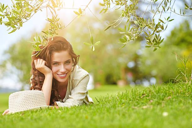 아름다운 웃는 여자 놓여 있음-잔디, 야외. 스톡 사진