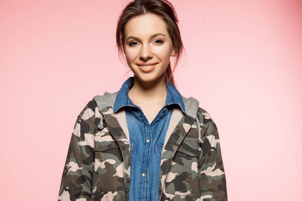 wunderschöne lächelnde frau auf einem rosa hintergrund in eine militärische jacke mit camouflage-muster - flecktarn stock-fotos und bilder
