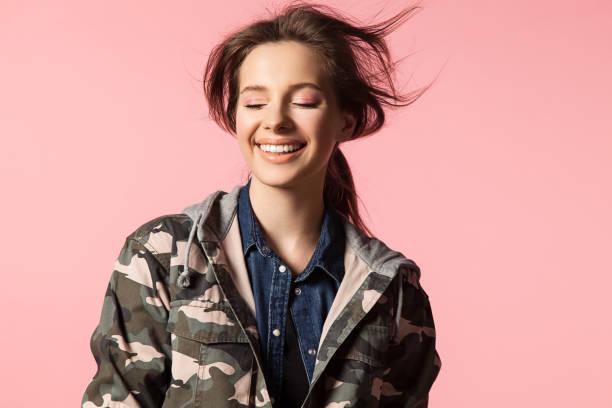wunderschöne lächelnde frau auf einem rosa hintergrund mit fliegenden haare in eine militärische jacke mit camouflage-muster - vogue muster stock-fotos und bilder