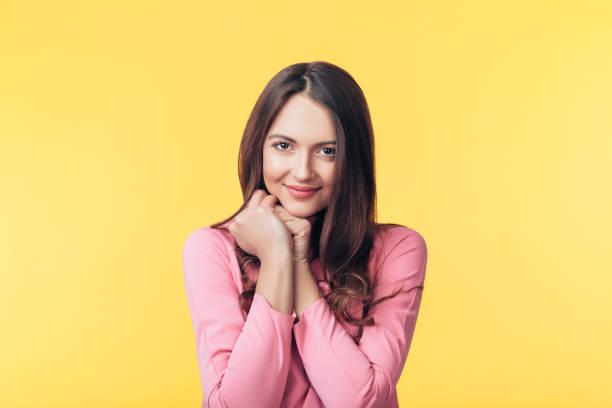 Schöne lächelnde Frau posiert über gelbem Hintergrund – Foto