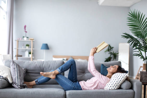 Beautiful smiling woman reading a book and lying on the sofa in the living room. stock photo