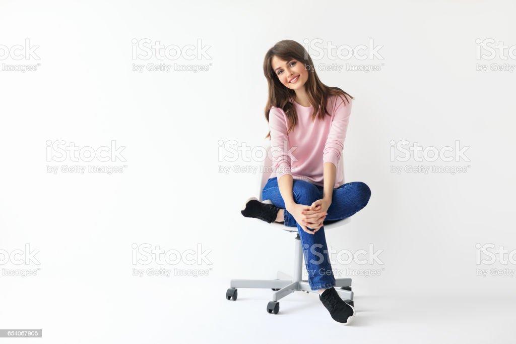 Wunderschöne lächelnde Frau auf Stuhl sitzend mit Textfreiraum – Foto