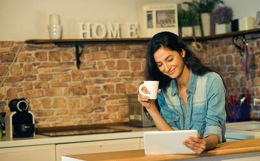 Beautiful smiling woman using digital tablet at home.