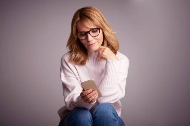 Wunderschöne lächelnde Frau mit ihrem Handy und SMS-Nachrichten – Foto