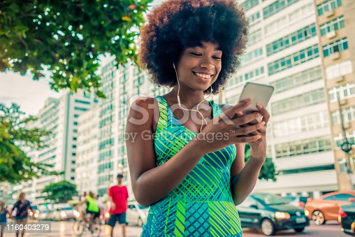 fit young woman relaxing after training in the city and using her smartphone