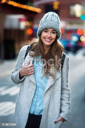 istock Beautiful smiling woman walking on the New York City street 513812036