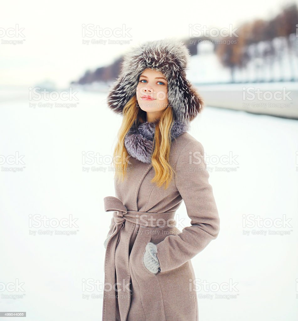 Beautiful smiling woman wearing coat and hat in winter stock photo