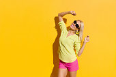 Happy beautiful blond woman in sunglasses, yellow shirt and pink shorts is standing with arms raised and looking at camera. Three quarter length studio shot on yellow background.