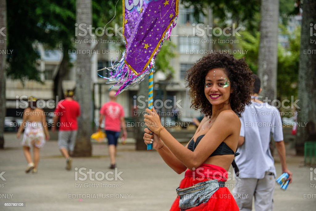 Beautiful smiling woman with curly hair and nose piercing, holding purple flag at Bloco Orquestra Voadora, Carnaval 2017 stock photo
