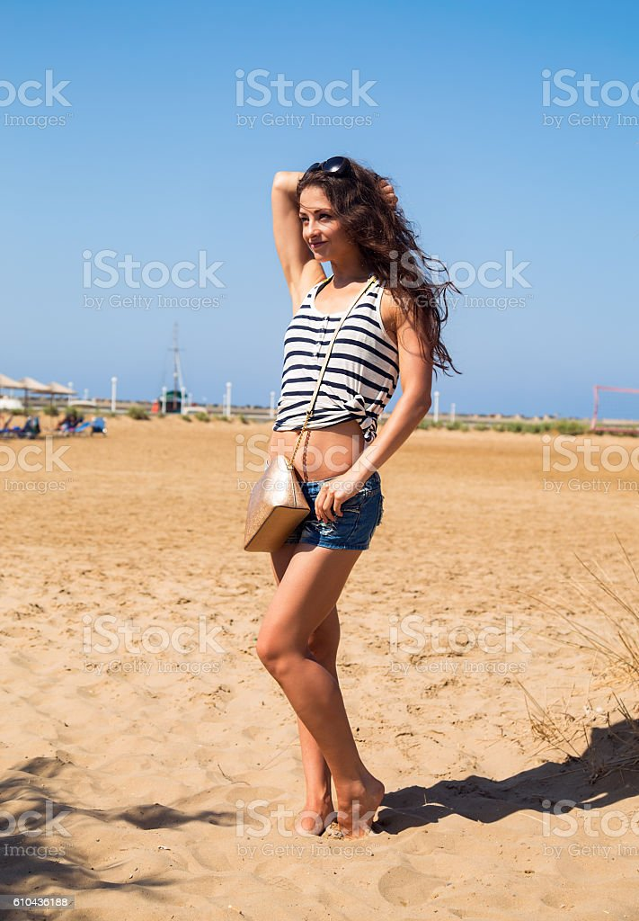 Beautiful smiling woman with fashion bag posing on the beach stock photo