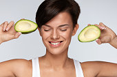 Beautiful Smiling Woman With Green Avocado Halves In Hands. Diet