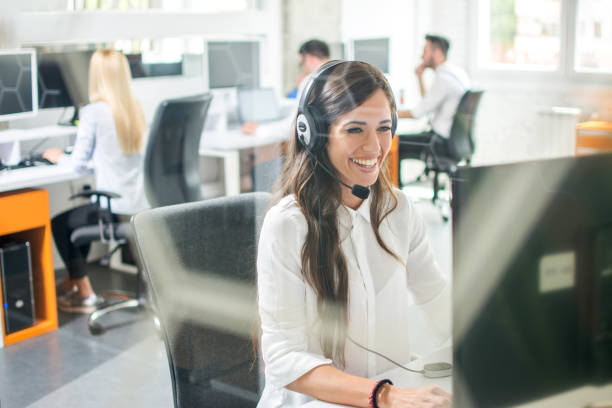 Beautiful smiling woman with headphones using computer while counseling at call center Beautiful smiling woman with headphones using computer while counseling at call center call centre photos stock pictures, royalty-free photos & images