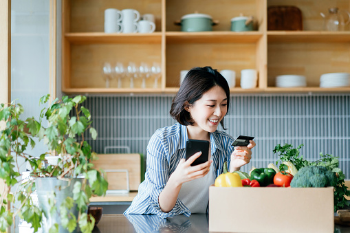 Beautiful smiling young Asian woman grocery shopping online with mobile app device on smartphone and making online payment with her credit card, with a box of colourful and fresh organic groceries on the kitchen counter at home