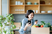 istock Beautiful smiling young Asian woman grocery shopping online with mobile app device on smartphone and making online payment with her credit card, with a box of colourful and fresh organic groceries on the kitchen counter at home 1272443174