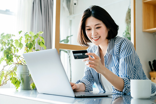 Beautiful smiling young Asian woman managing online banking with her laptop and credit card over the kitchen counter at home. Technology makes life so much easier