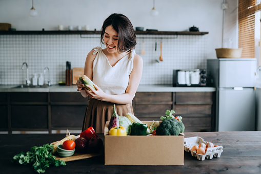 Beautiful smiling young Asian woman received a full box of colourful and fresh organic groceries ordered online by home doorstep delivery service. She is sorting out the groceries and preparing to cook a healthy meal