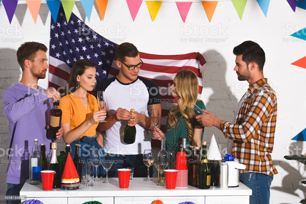 beautiful smiling young friends drinking wine at home party stock photo