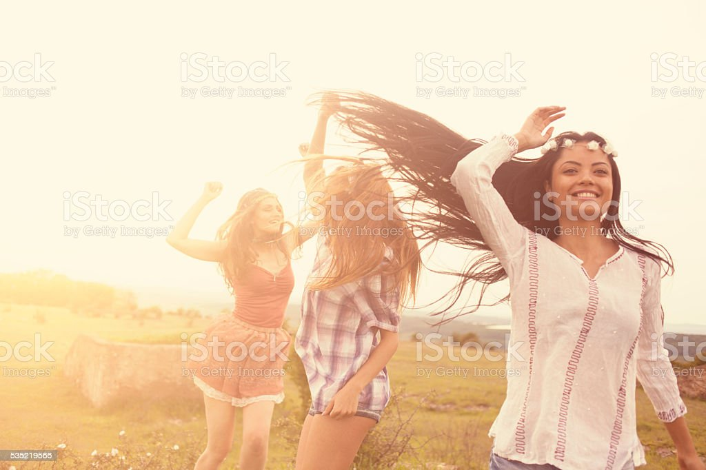 Beautiful smiling young hipster women dancing in the grassland stock photo