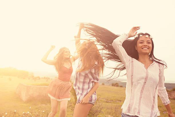 schönen lächeln junge hipster frauen tanzen in der grassland - hippie kleider stock-fotos und bilder