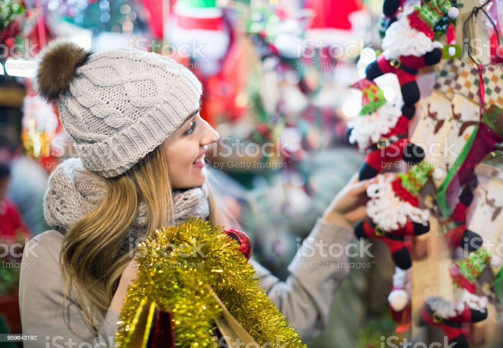 Hermosa joven sonriente elegir la decoración de la Navidad - Foto de stock de Abrigo libre de derechos