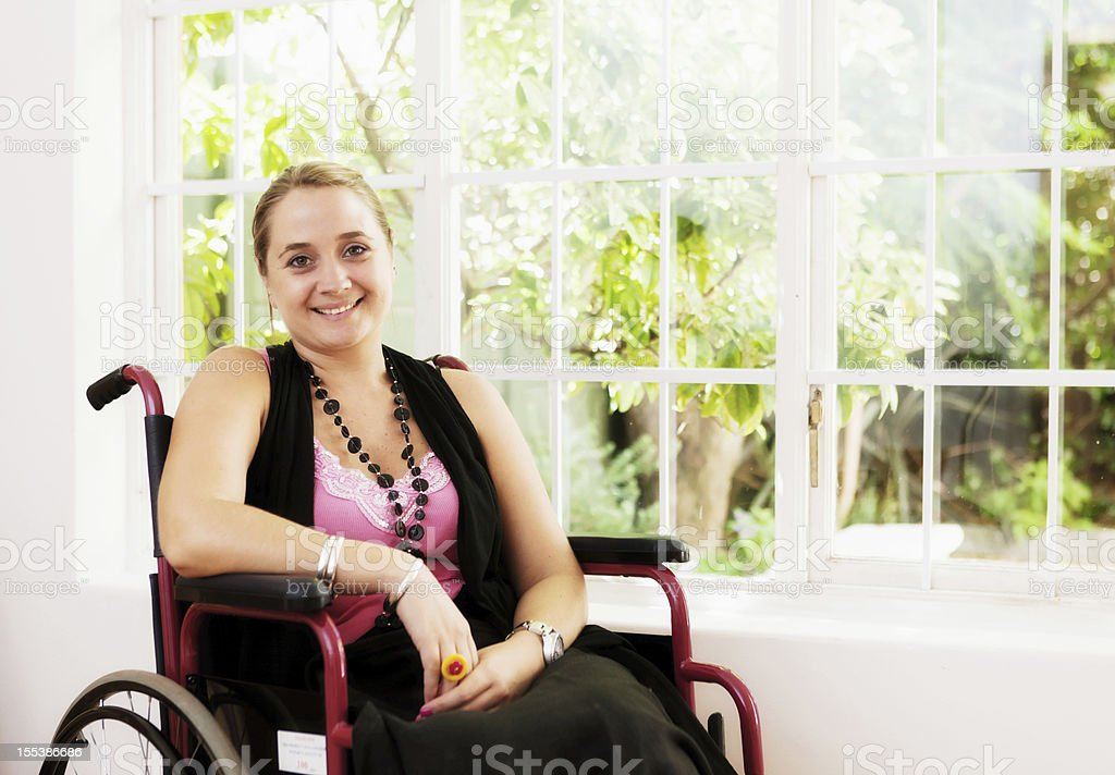 Beautiful smiling young woman in wheelchair by window stock photo