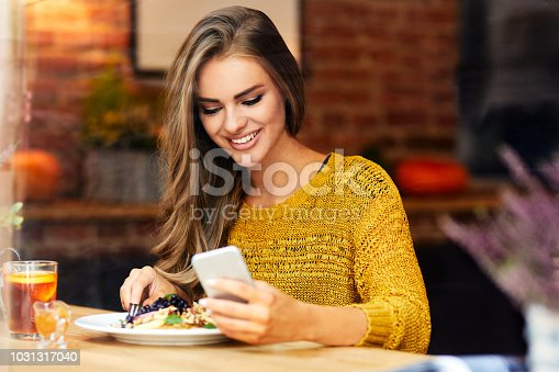 Beautiful smiling young woman looking at phone while sitting and eating in a cafe