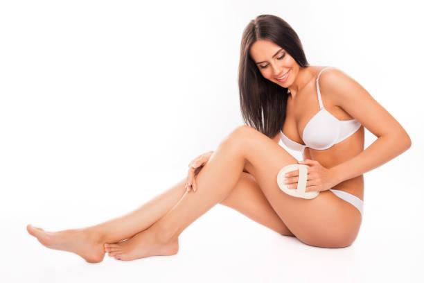 schöne lächelnde junge frau macht eine peeling-massage - peeling bürste stock-fotos und bilder