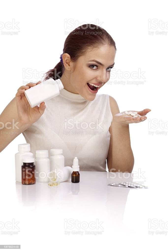 Beautiful smiling young woman showing a pill bottle. XXXL royalty-free stock photo