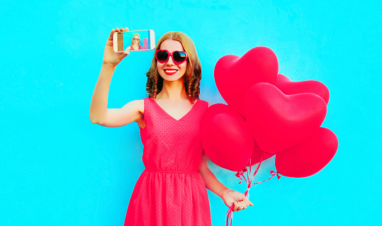 istock Beautiful smiling young woman taking selfie picture by phone with pink heart shaped air balloons on colorful blue background 1130327319